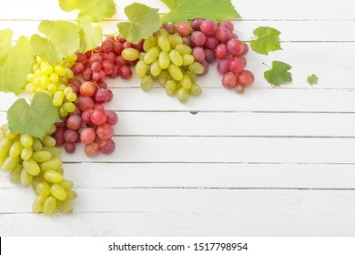 pink and green grape on wooden background