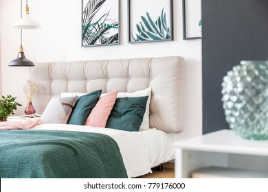 Pink and green pillows on bed with beige bedhead and lamps in modern bedroom interior with floral posters