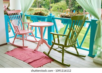 Pink and green wooden rocking chairs and table on porch or balcony. Two relaxing armchairs on porch of luxury hotel. Empty cafe with rocking chairs and table on summer  terrace outdoor, copy space