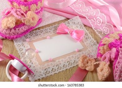 Pink greeting card with tiny girls booties and pacifier