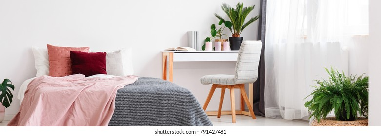 Pink and grey bedsheets on bed in cozy bedroom interior with chair at desk with plants, candles and books
