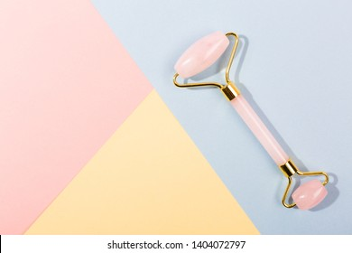 Pink Gua Sha facial massage tools. Rose Quartz jade roller on pink background. Anti age, lifting and toning treatment at home. Copy space.