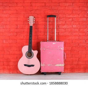 pink guitar and vintage pink travel suitcase
