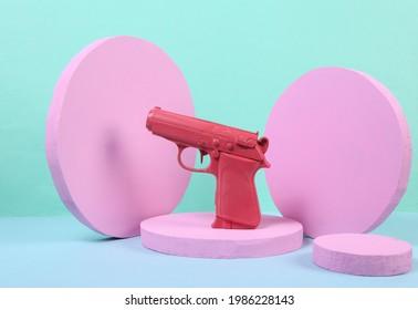 Pink gun on podium with geometric shapas. Concept art. Minimalism