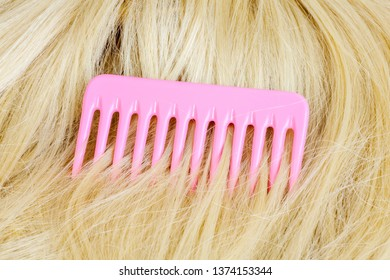 Pink hairbrush on wig in blond color