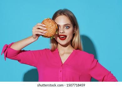 Pink hamburger shirt blue background charming woman bright makeup blonde