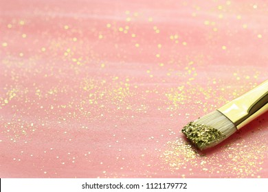 Pink hand-painted paper with brush and   gold glitter. Selective focus.
