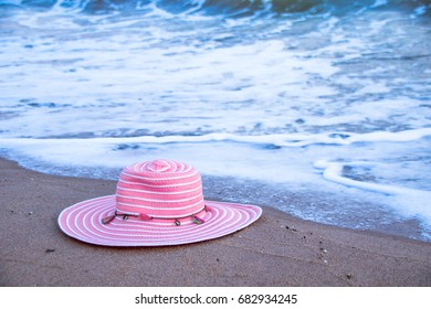 Pink hat is placed on the beach. With a sea wave background.