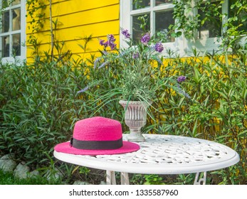 Pink hat placed on  table, relaxing corner in coffee shop.