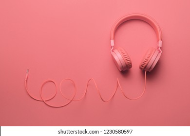 Pink headphones on pink background. Music concept