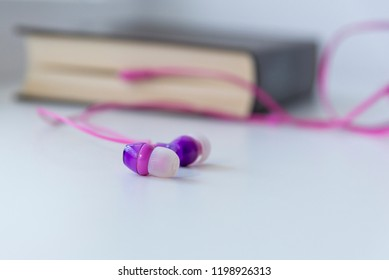 Pink headphones sticking out of a book on a light background, the theme of an audiobook