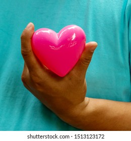 Pink heart in hand on blue background , Concept valentine day.