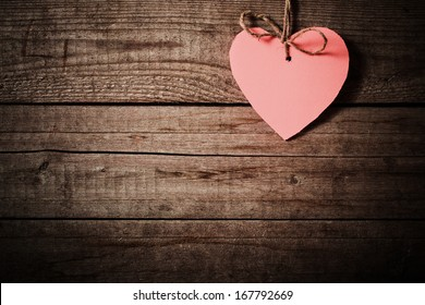 pink  heart made of paper on wooden background