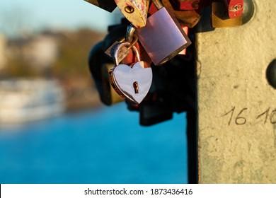 Pink heart padlock between different padlocks at the bridge . Frankfurt Eiserner Steg, padlocks attached to the bridge railing.