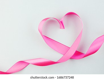 pink heart ribbon isolated on a blue background. silk fabric in the form of a heart. background for Valentine's day