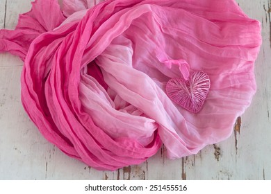 Pink heart with scarf on rustic background