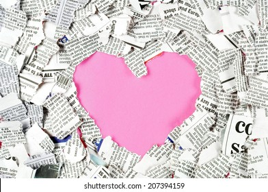 Pink heart shape in the middle of shredded newspaper pieces.