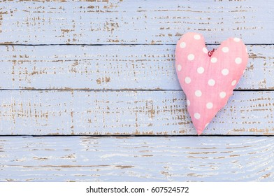 Pink heart shape on pastel blue wooden background for girl birthday baby shower party.