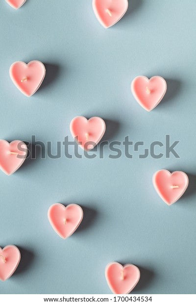 pink heart shaped candles on blue background. Valentines day minimalist background. pink heart, love symbol, graphic design element for greeting cards