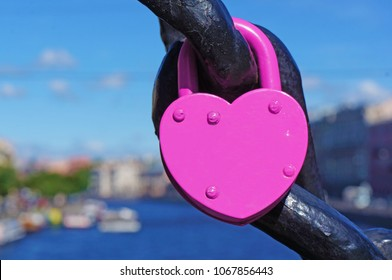 Pink heart shaped lock, canal with boats on the background.