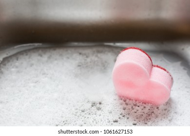 Pink heart sponge in the used sink full of foam