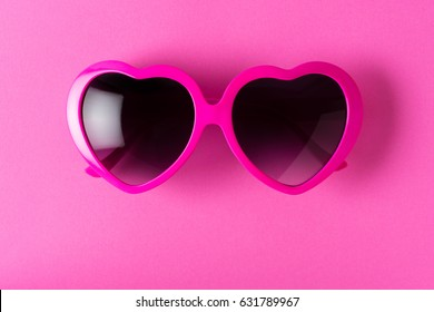 Pink heart-shaped sunglasses isolated on pink background