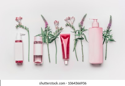 Pink herbal natural facial cosmetic products set with herbs and flowers on white background, top view. Branding mock up