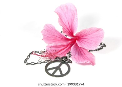 pink hibiscus flower with silver peace pendant as symbol of 1960's flower power