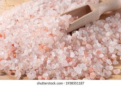 Pink himalayan salt. Close-up Himalayan Pink Rock Salt In wooden Spoon on black background. Fine grains of Pink Himalayan salt