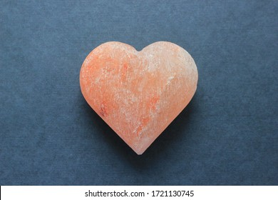 pink Himalayan salt heart shape figure, love concept for Valentine's Day, on gray background, love concept for Valentine's Day on February 14, spa, therapy