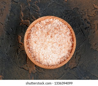 Pink himalayan salt in wooden bowl on black background.