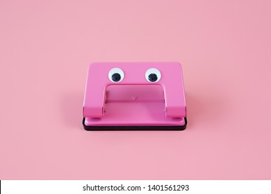 Pink hole puncher with cute fake eye on pink background