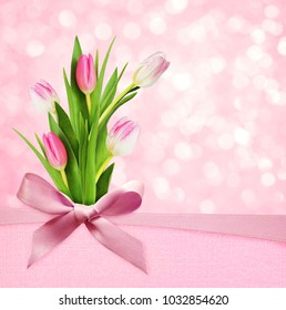 Pink holiday bokeh background with silk bow and tulip flowers bouquet