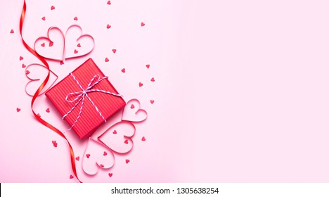 Pink holiday Valentine's background with present gift box and little hearts on background. Valentine's day greeting concept. Top view, flat lay.