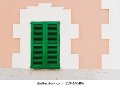 Pink house facade with green shutter