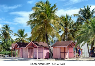 Pink huts among palm trees in Antigua island in the Caribbean