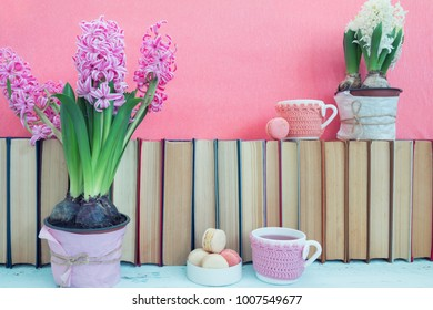 Pink hyacinths, macaroons, tea cups and white hyacinths near pile of books at pink background. Beautiful spring pink background. Copy space.