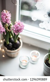 Pink hyacinths in a wooden tub, candles in transparent candlesticks with garland lights on a white ceramic window sill with a view on the window and New Year's stickers on it, top view.