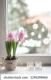 Pink hyacinths in a wooden tub, candles in transparent candlesticks and garland lights on a white ceramic window sill with a view on the window and New Year's stickers on it.