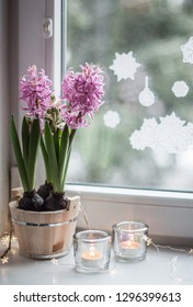 Pink hyacinths in a wooden tub, candles in transparent candlesticks and garland lights on a white ceramic window sill with a view on the window and New Year's stickers on it, closeup.