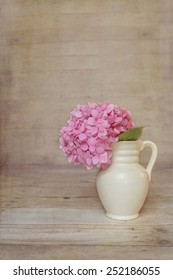 Pink Hydrangea in a antique pitcher with a rustic wood background with copy space.
