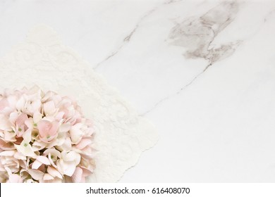 Pink hydrangea blossom and white lace background with copy space against white marble.