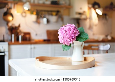 Pink hydrangea flower on wooden serving tray. Morning kitchen scene. Cozy home atmosphere hygge. Spring still life on table for Women Day.