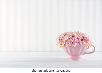 Pink hydrangea flowers in a shabby chic mug on vintage background with copy space
