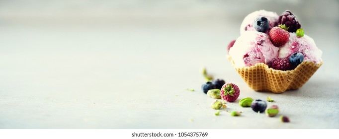 Pink ice cream with berries, strawberries, blueberries, raspberries, pistachios in waffle basket. Summer food concept, copy space. Healthy gluten free fruit ice-cream. Banner.