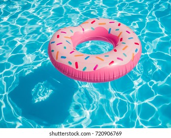 Pink inflatable donut swimming ring in a swimming pool