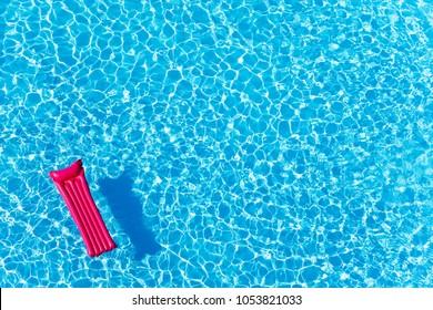rosafarbene, aufblasbare Matratze auf Wasseroberfläche schwimmend