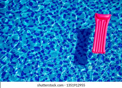 pink inflatable mattress on blue turquoise water swimming pool copy space top view