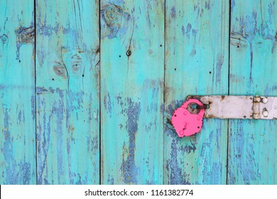 Pink iron lock hanging on blank antique rustic teal blue wooden door; love concept background with painted wood copy space