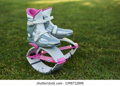 pink kangoo jumping fitness boots at green grass background. fitness training background. sport concept
